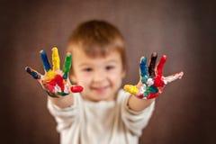 Kleiner Junge mit den gemalten Händen Stockbild