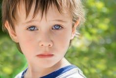 Kleiner Junge mit den schönen blauen Augen, die, frustriert traurig schauen, stockfotografie
