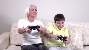 Kleiner Junge mit der Mutter, die zu Hause Videospiele, slowmotion spielt stock footage