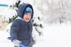 Kleiner Junge mit der Schaufel, die im Schnee spielt Lizenzfreie Stockfotografie