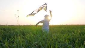 Kleiner Junge mit Drachen in Hände läuft am Feld im Sonnenlicht auf Hintergrundhimmel stock footage