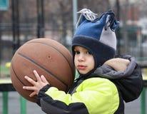 Kleiner Junge mit einem Basketball Stockfotografie