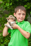 Kleiner Junge mit einem Kaninchen in seinen Händen Lizenzfreies Stockbild