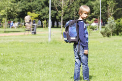 Kleiner Junge mit einem Rucksack gehen zur Schule Rückseitige Ansicht Stockbilder