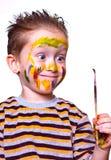 Kleiner Junge mit einem schmutzigen Gesicht, das den Pinsel betrachtet Lizenzfreie Stockbilder