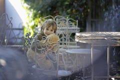 Kleiner Junge mit einem Teddybären, der auf dem Stuhl sitzt Lizenzfreie Stockfotos