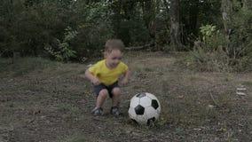 Kleiner Junge mit einer Kugel im Park stock footage