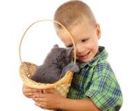 Kleiner Junge mit grauer Miezekatze in der Flechtweide Lizenzfreie Stockfotos