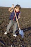 Kleiner Junge mit großer Schaufel Stockfotografie