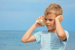 Kleiner Junge mit hörenden Geräuschen des Shells von Meer Lizenzfreies Stockfoto
