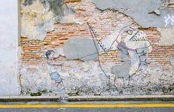 Kleiner Junge mit Haustierdinosaurier auf der Wand berühmten Straße Art Mural in George Town, Penang-UNESCO-Bauerbe, Malaysia Stockbild