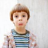 Kleiner Junge mit lustigem Gesicht Lizenzfreies Stockfoto