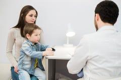 Kleiner Junge mit Mama auf Steuerpädiatrischem Besuch in der Arztpraxis Lizenzfreies Stockbild