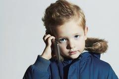 Kleiner Junge mit Mobiltelefon modernes Kind im Wintermantel Kinder in der erwachsenen Kleidung Kinder Lizenzfreie Stockbilder