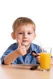 Kleiner Junge mit Orangensaft Stockbilder