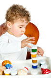 Kleiner Junge mit Ostereiern und Farbe Stockbild