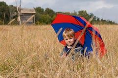 Kleiner Junge mit Regenschirm Stockfotos