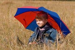Kleiner Junge mit Regenschirm Stockfoto