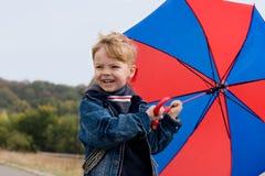 Kleiner Junge mit Regenschirm Stockbild