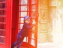 Kleiner Junge mit roter Telefonzelle in der Stadt Stockfotografie