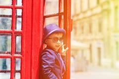 Kleiner Junge mit roter Telefonzelle in der Stadt Stockbild