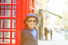 Kleiner Junge mit roter Telefonzelle in der Stadt Lizenzfreie Stockfotografie
