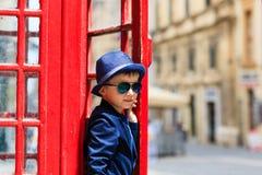 Kleiner Junge mit roter Telefonzelle in der Stadt Lizenzfreie Stockbilder