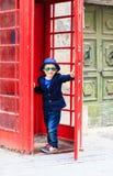 Kleiner Junge mit roter Telefonzelle in der Stadt Lizenzfreie Stockfotos