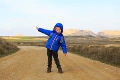 Kleiner Junge mit Rucksackreise auf der Straße Lizenzfreies Stockfoto