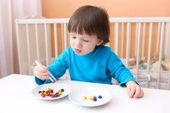 Kleiner Junge mit Scheren und Perlen Pädagogisches Spielen Stockbild