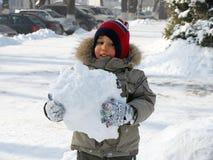 Kleiner Junge mit Schneeball Stockfoto