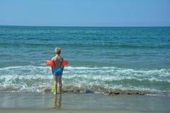 Kleiner Junge mit Schwimmenärmeln, Stände auf dem Strand Lizenzfreies Stockbild