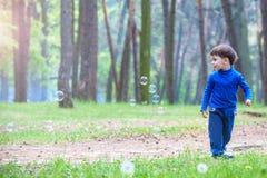 Kleiner Junge mit Seifenblasen im Sommerpark Lizenzfreie Stockbilder