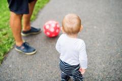 Kleiner Junge mit seinem Vater, der erste Schritte macht stockfotos