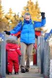 Kleiner Junge mit seinem Vater/Großvater, die Spaß zusammen im Park des verschneiten Winters haben Lizenzfreies Stockbild
