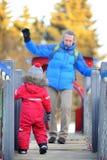 Kleiner Junge mit seinem Vater/Großvater, die Spaß zusammen im Park des verschneiten Winters haben Lizenzfreies Stockfoto