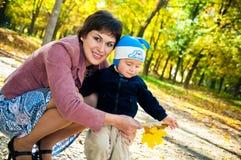 Kleiner Junge mit seiner Mutter, die in den Park geht Stockfotografie