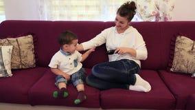 Kleiner Junge mit seiner Mutter, die im Raum im dem Couch und Uhr Fernsehen sitzt stock footage