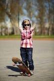 Kleiner Junge mit Skateboard auf der Straße Lizenzfreie Stockbilder