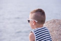 Kleiner Junge mit Sonnenbrille und gestreifter Weste untersucht den Abstand des Meeres Stockfotos