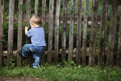 Kleiner Junge mit Zaun draußen stockfoto