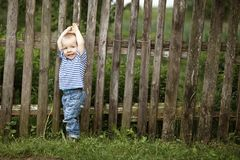 Kleiner Junge mit Zaun draußen stockfotografie