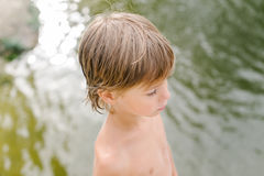 Kleiner Junge nahe Wasser am Strand am heißen Sommertag Lizenzfreie Stockfotografie