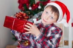 Kleiner Junge nahe Weihnachtsbaum mit Geschenken Lizenzfreies Stockfoto