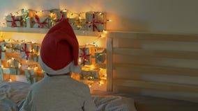 Kleiner Junge nimmt ein Geschenk von einem Einführungskalender, der an einem Bett hängt, das mit Weihnachtslichtern erleichtert w stock footage