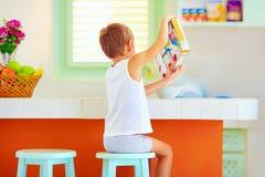 Kleiner Junge ohne Hilfe, der morgens Frühstück zu Hause zubereitet Stockfotografie