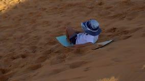 Kleiner Junge reitet den Pferdeschlitten hinunter eine Düne in einer roten Wüste stock footage