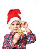 Kleiner Junge in rotem Sankt-Hut mit goldenem Stern Lizenzfreies Stockbild