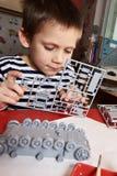 Kleiner Junge sammelt vorbildlichen Plastikbehälter Stockfotografie