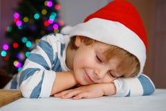 Kleiner Junge in Sankt-Hut mit Weihnachtsbaum und Lichtern Lizenzfreie Stockfotos